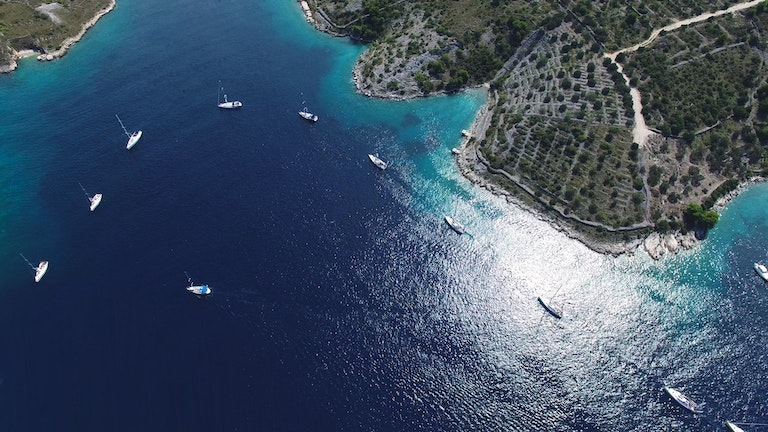 Arial view of boats in a line in a bay.